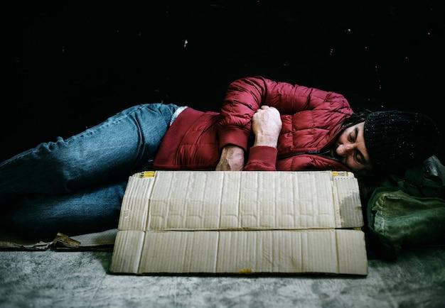 路上で寝ているホームレスの男性