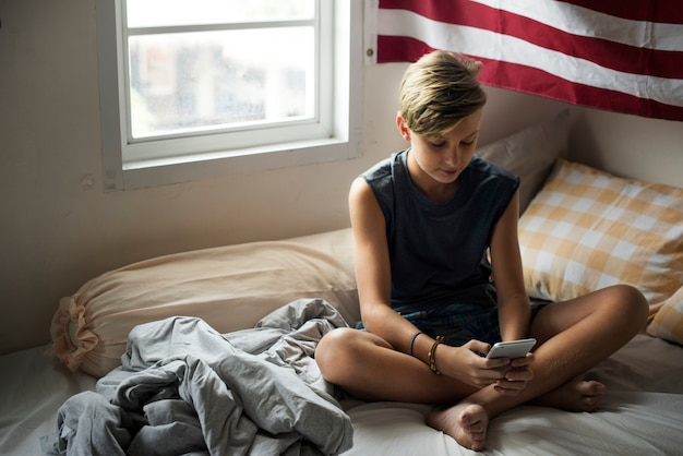 携帯電話を使用してベッドの上に座っている若い白人少年