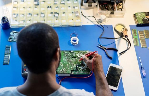コンピューター電子部品とマルチメーターを使用して技術者