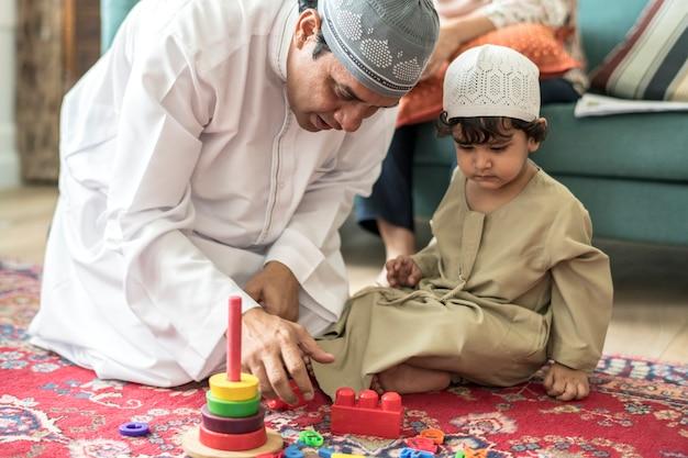 家でリラックスして遊ぶイスラム教徒の家族