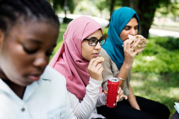 多様な学生のグループが一緒に昼食を食べています