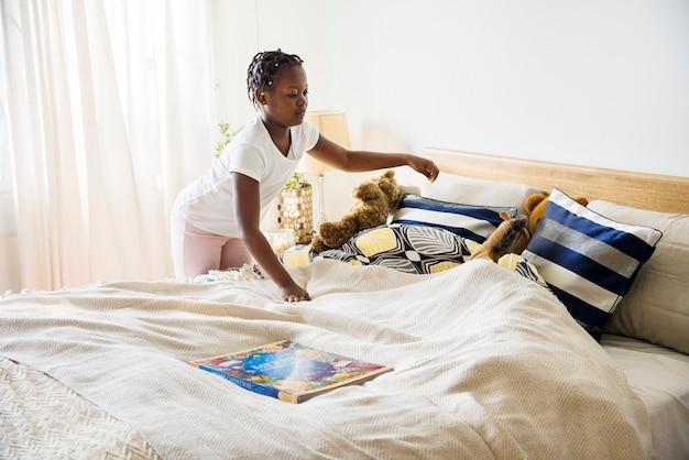 寝室を作る若い十代の少女