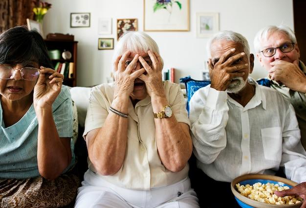 Старшие друзья сидят на диване с ужасом реакции