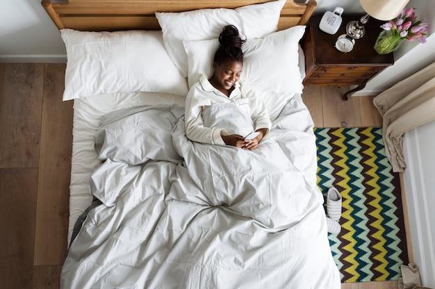 携帯電話を使用してベッドの上の笑顔のアフリカ系アメリカ人女性