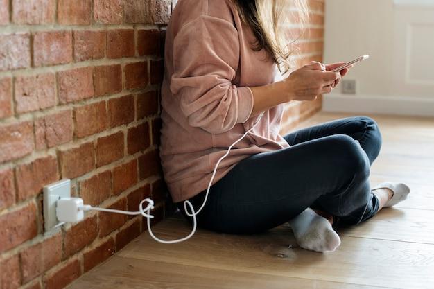 それが充電されているとしてスマートフォンを使用して若い女性