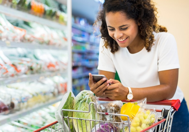 Женщина покупает овощи в супермаркете
