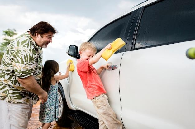 白い車を洗う家族