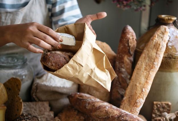 Женщина продает сыр покупателю в фермерском магазине
