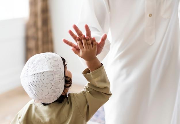 ハイファイブを与えるイスラム教徒の少年