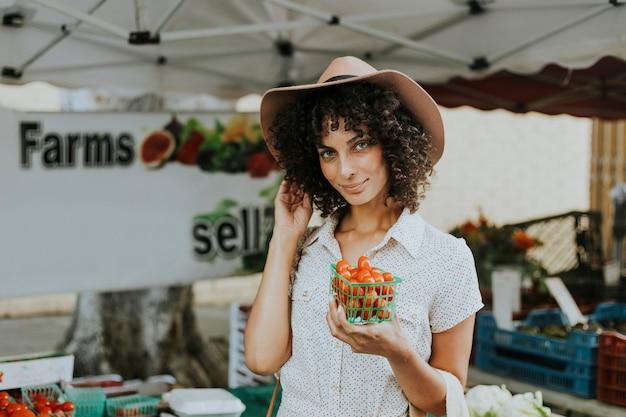 美しい女性の農民市場でトマトを買う