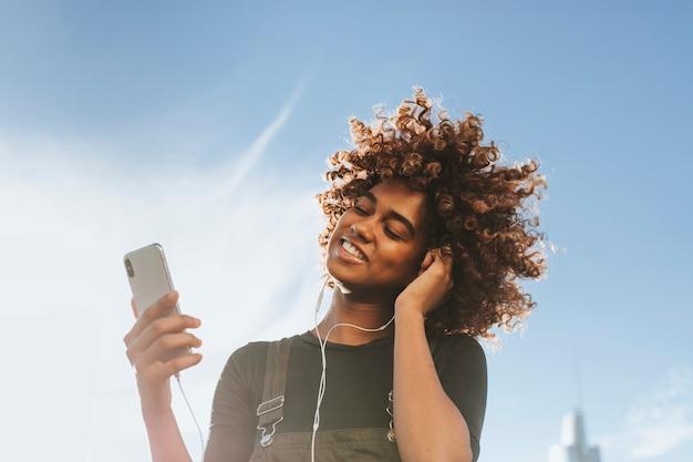 彼女の電話から音楽を聴いている女の子