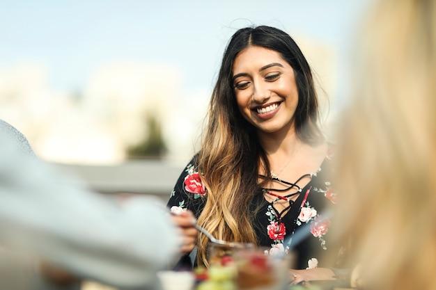Веселая женщина наслаждается вечеринкой на крыше со своими друзьями