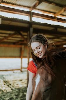 栗の馬をグルーミングする女の子