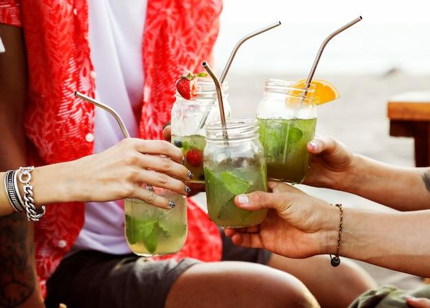 Разнообразные друзья наслаждаются пляжной вечеринкой