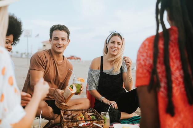ビーチピクニックで食べ物を食べている友人