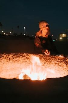 焚き火でマシュマロを焙煎する女