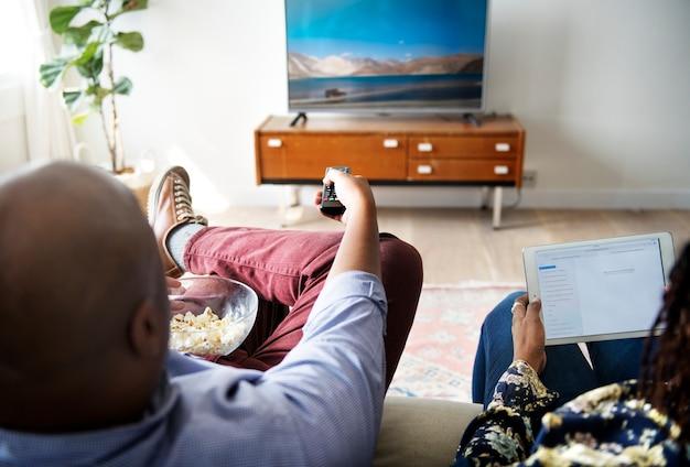 家で一緒にテレビを見ているカップル