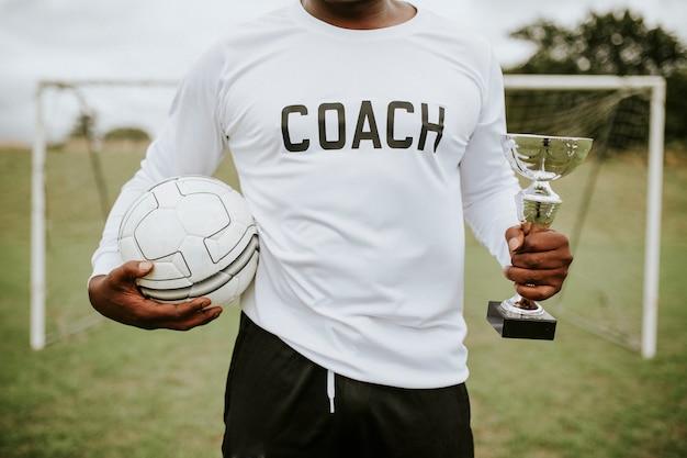 サッカーコーチのトロフィーカップとボールを保持