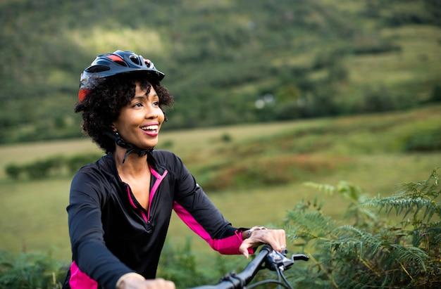 Веселая женщина велосипедист, наслаждаясь на велосипеде