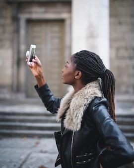 彼女の電話で写真を撮る女性観光客