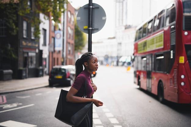 ロンドンのダウンタウンの通りを渡るお下げを持つ女性