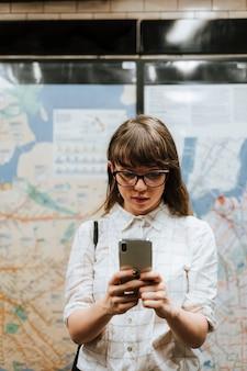 Девушка текстовые сообщения в ожидании поезда на платформе метро