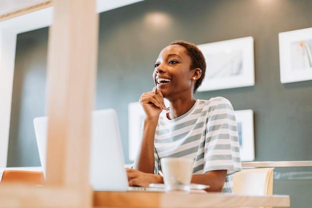 カジュアルな女性がカフェで働く