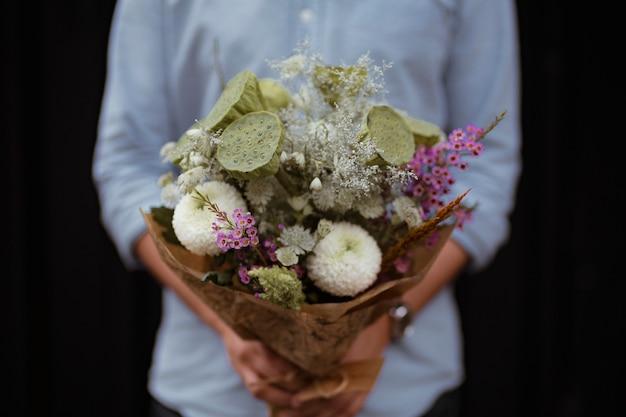 白いダリアの花の花束を持って男