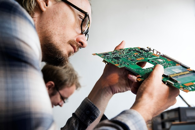 コンピューターのメインボードに取り組んでいる技術者の側面図