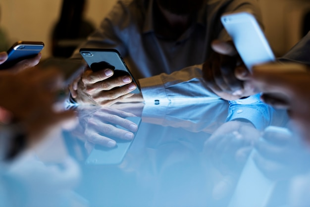 一緒に座っているスマートフォンを持っている手