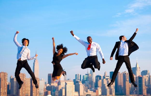 多様なビジネス人々のグループがジャンプしています