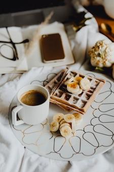 Тарелка с вафлями на завтрак с банановой начинкой на белой кровати рядом с дневником и телефоном