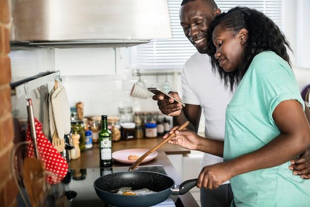 台所で揚げ卵を調理するカップル
