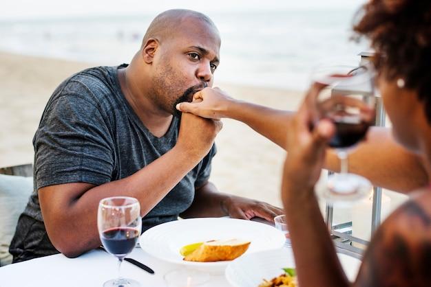 ビーチでロマンチックな夕食を持っているカップル