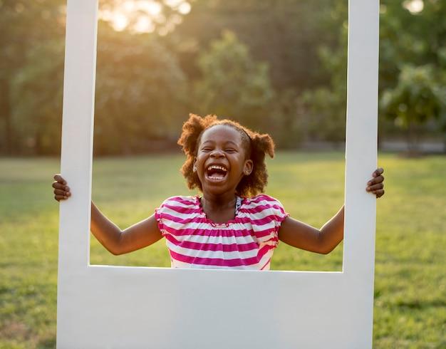 アフリカ系の女の子は公園でフレームを保持しています。