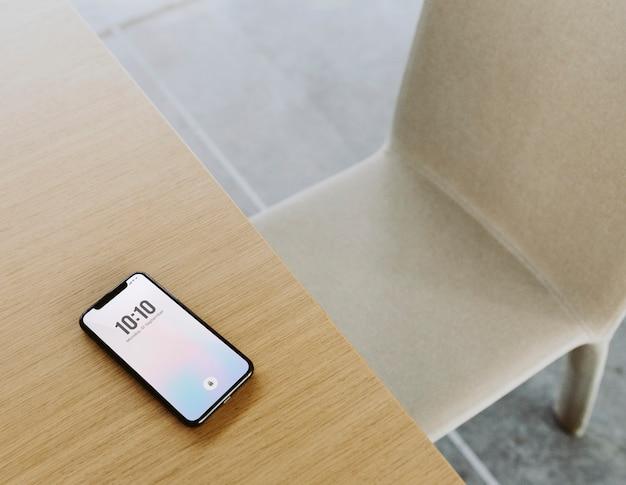 木製のテーブルに日付と時刻を示す携帯電話
