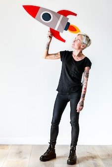 Татуированная женщина, держащая значок ракеты