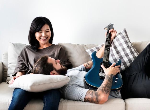 ギター音楽と愛の概念を演奏するソファのボーイフレンドにかわいいカップル