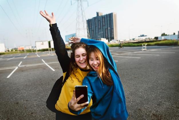 Девушка друзья улыбаясь и принимая селфи вместе