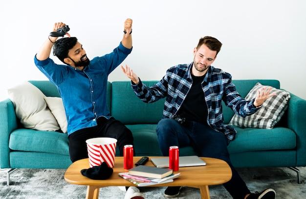 Мужчины играют в видеоигры на диване