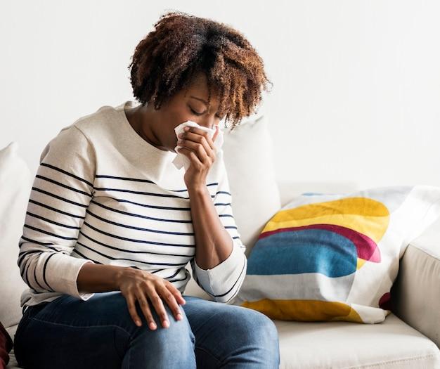 女性が自宅でソファに病気