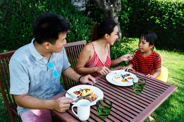 Мать кормит сыном завтрак