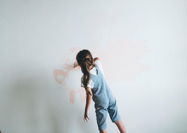 ピンクの壁を塗る少女