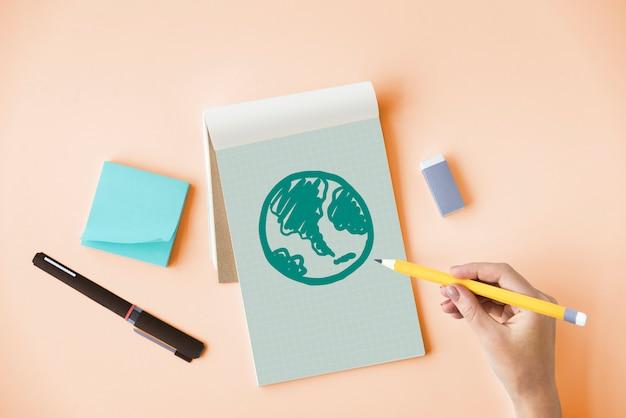 メモ帳に緑の地球儀を描く手