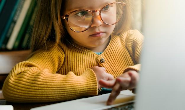 Маленькая девочка с использованием цифрового ноутбука концепция электронного обучения