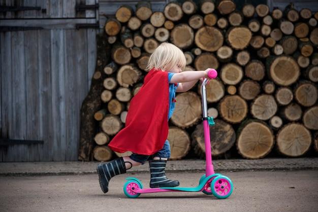 スクーターの愛らしい概念を使用してスーパーヒーローの男の子