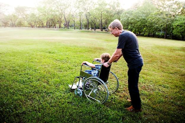 Маленький мальчик на инвалидной коляске с дедушкой в парке на открытом воздухе