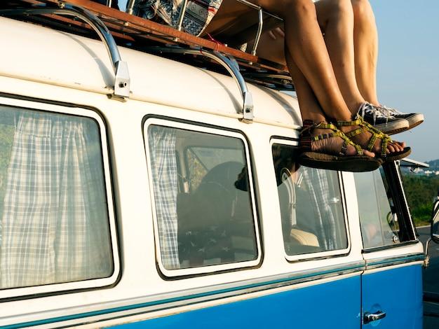 バンの旅の旅の屋根の上に座っている女性