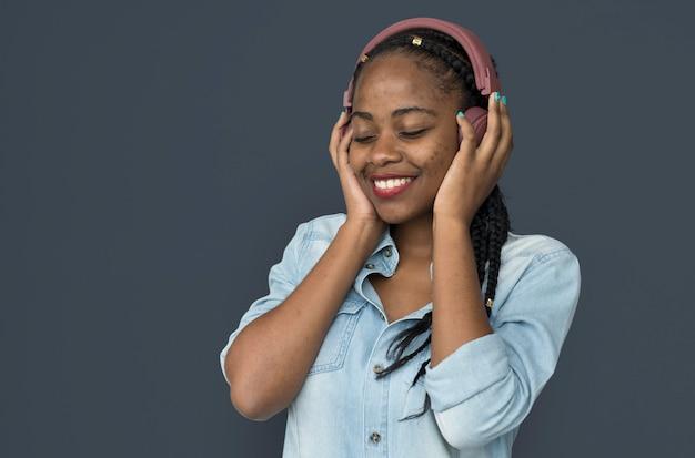 音楽ヘッドフォンを聞いて若い黒人少女
