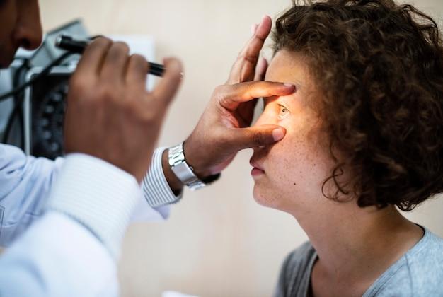 Молодая кавказская девушка получает осмотр глаз